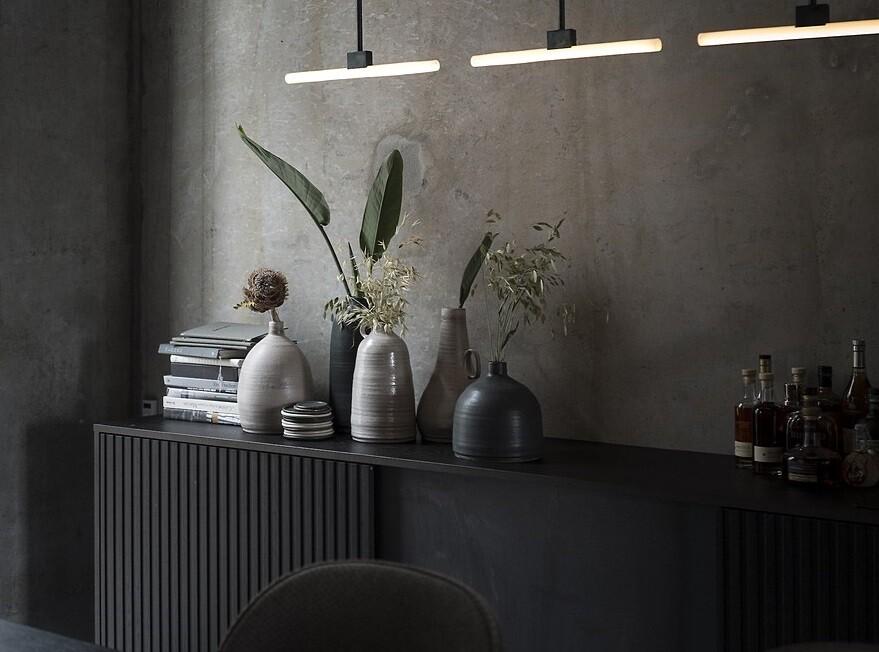 Copenhagen Restaurant Exhibiting Warm and Material Richness Against Raw Concrete Walls