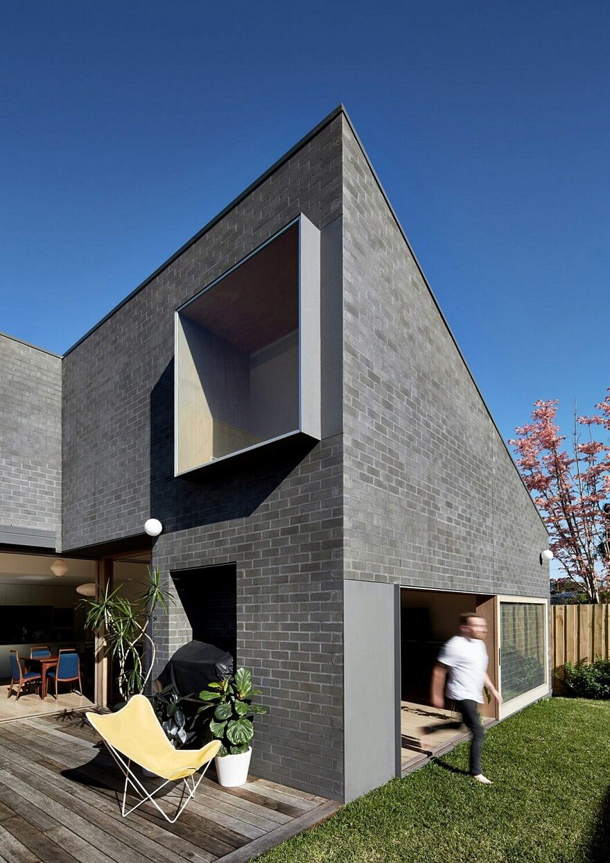 This black brick house features generous spaces with a Black brick homes