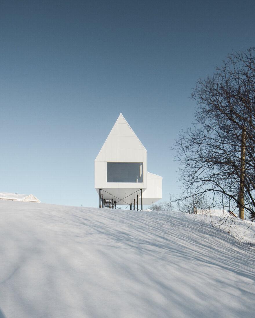Winter Chalet on Stilts Rises Above a Snow-Laden Slope in Quebec
